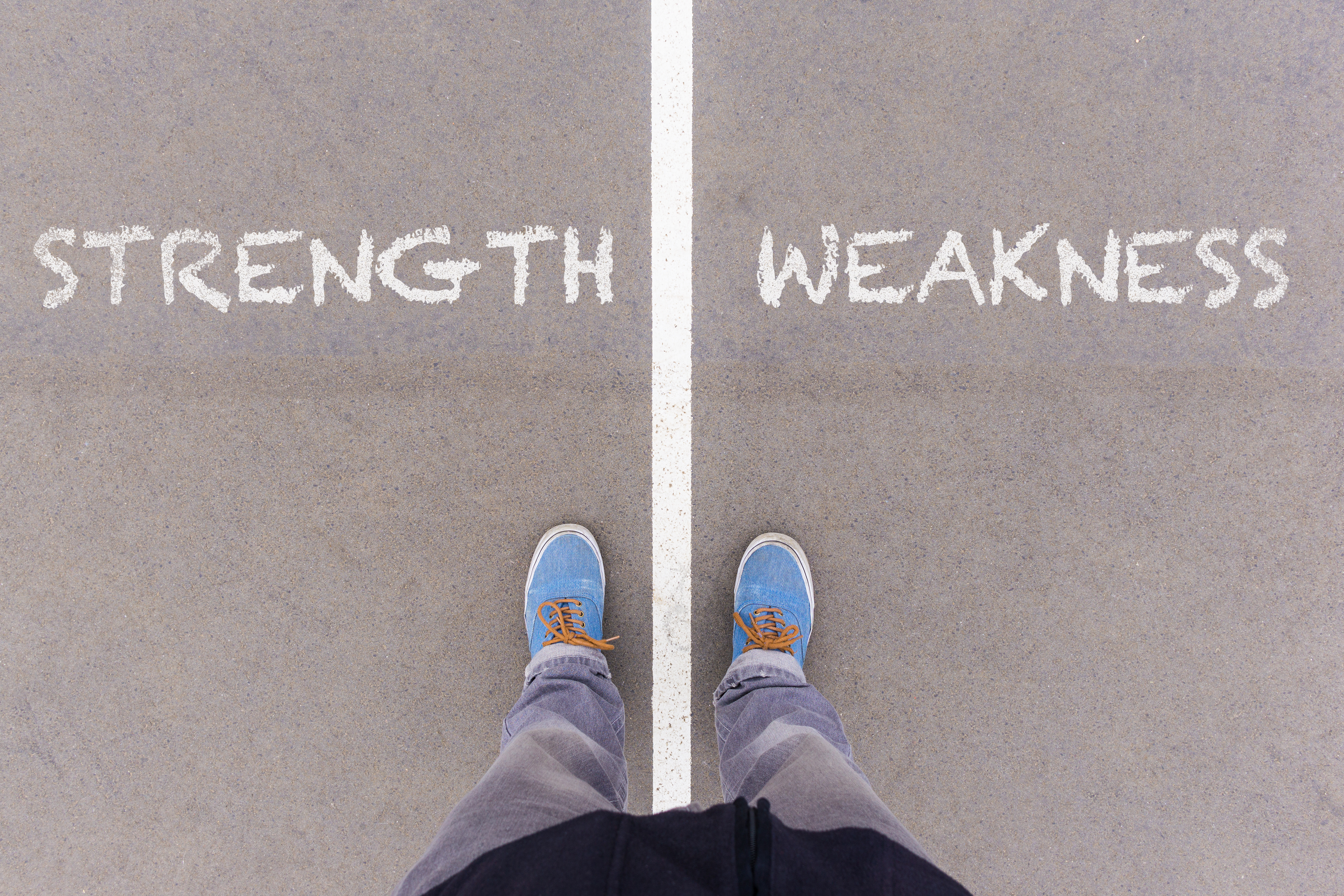 Strength and weakness text on asphalt ground, feet and shoes on